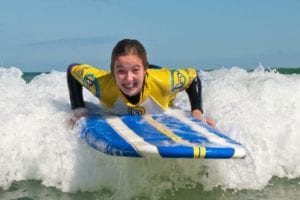 Girls go surfing at Harlyn Surf School Padstow Cornwall UK