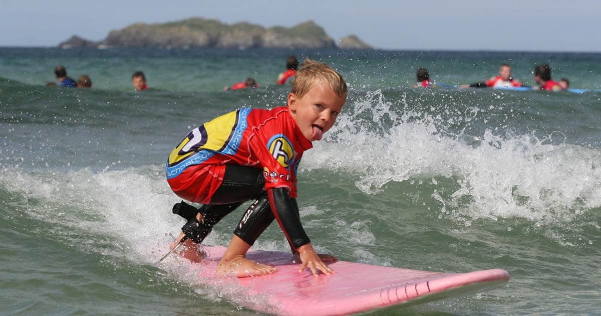 Surf School kid riding a wave