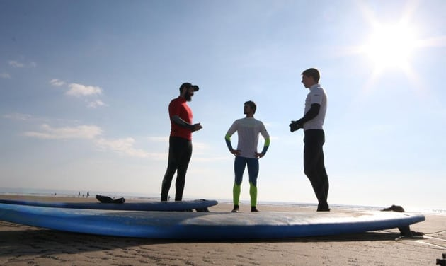 three surfers chatting on a beach